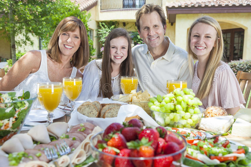 Parents Children Family Healthy Eating Outside. An attractive happy, smiling family of mother, father and two daughters eating healthy food at a table outside stock photo