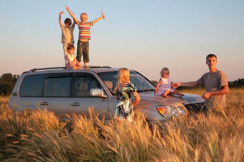 Parents and children on offroad car on wheaten fie. Parents and children on offroad car on a wheaten field royalty free stock photography