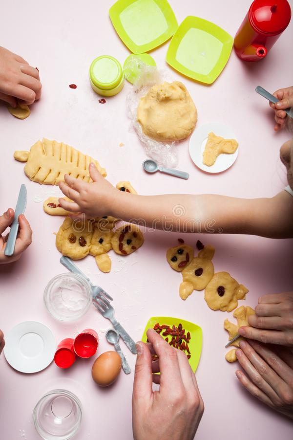 Parents and children play in the cook and kitchen. They make New Year cookies in the form of snowmen and a Christmas tree, close- stock photo
