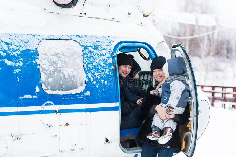 Parents with children prepare for flight by helicopter in snow weather. royalty free stock photos