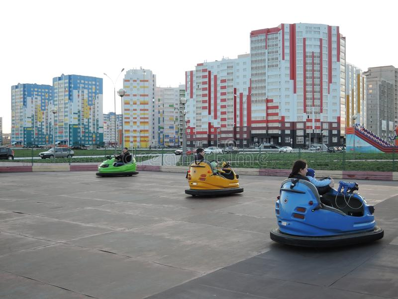 Parents with children ride on the rides - cars in the new district of the city. Russia, Penza - may, 2017. Parents with children ride on the rides - cars in the royalty free stock photography