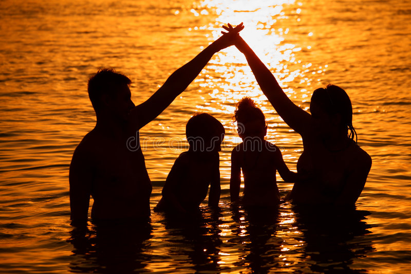 Parents with children in sea on sunset stock photography