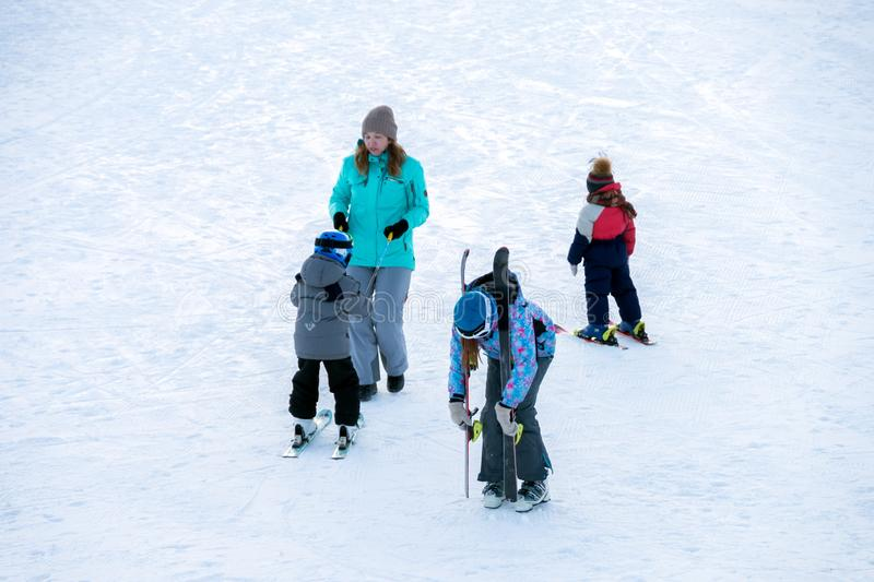 Parents and children skiing on the mountainside at the weekend royalty free stock photo