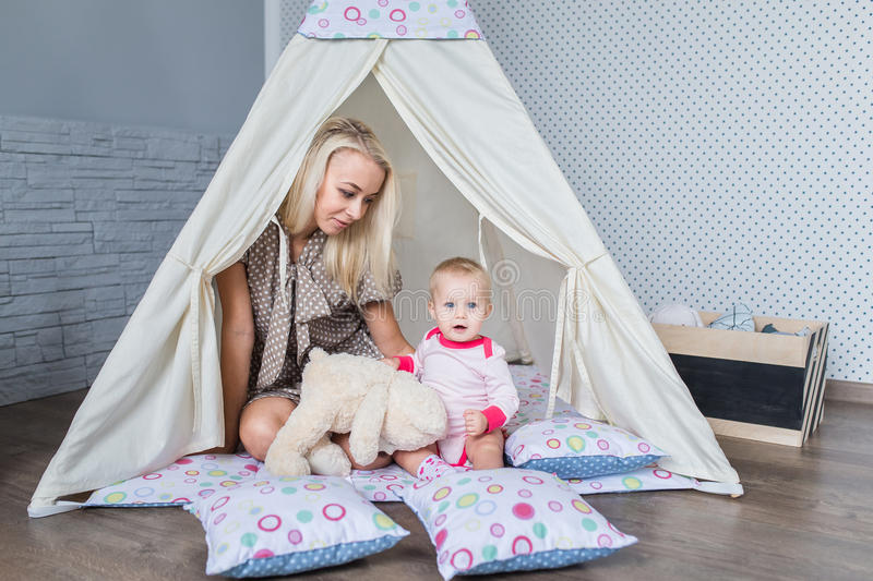 Parents with children in a teepee. Parents play with children in a teepee tent in the bright nursery royalty free stock photography