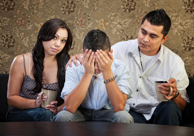 Parents Comforting Their Son. Latino parents comforting sad male teenager with hands in face royalty free stock photo