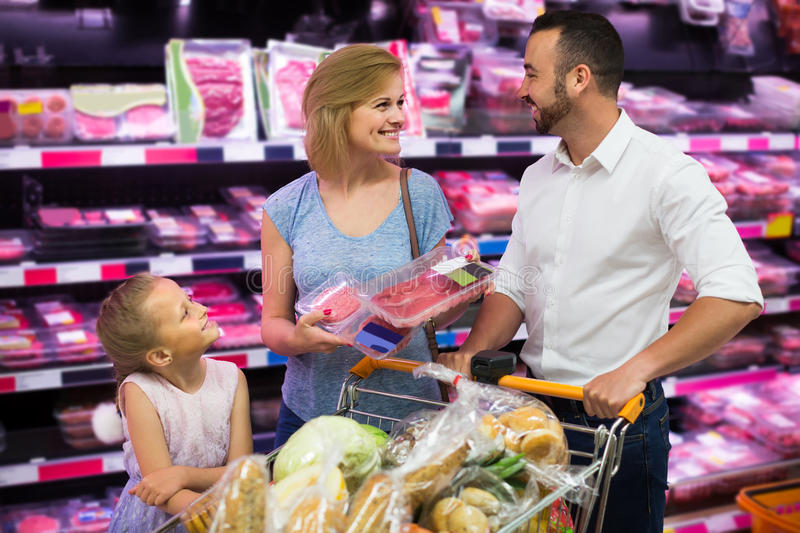 Parents with daughter choosing meat in refrigerated section in h stock photo