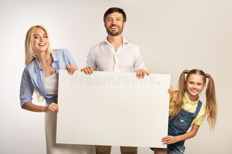 Parents And Daughter Holding White Board Smiling At Camera, Studio royalty free stock images