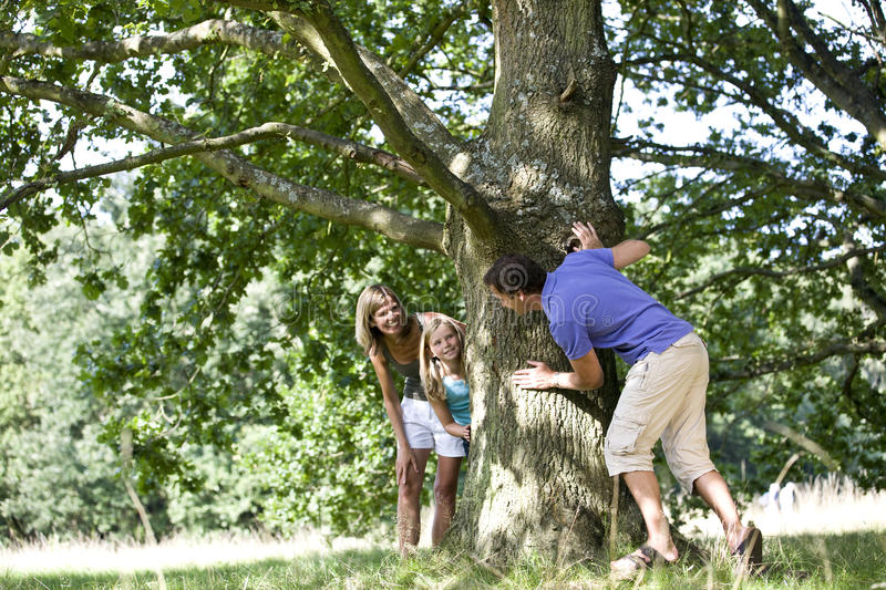 Parents and daughter playing hide and seek stock photography