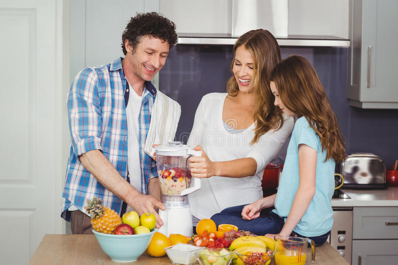 Parents and daughter preparing fruit juice royalty free stock photos