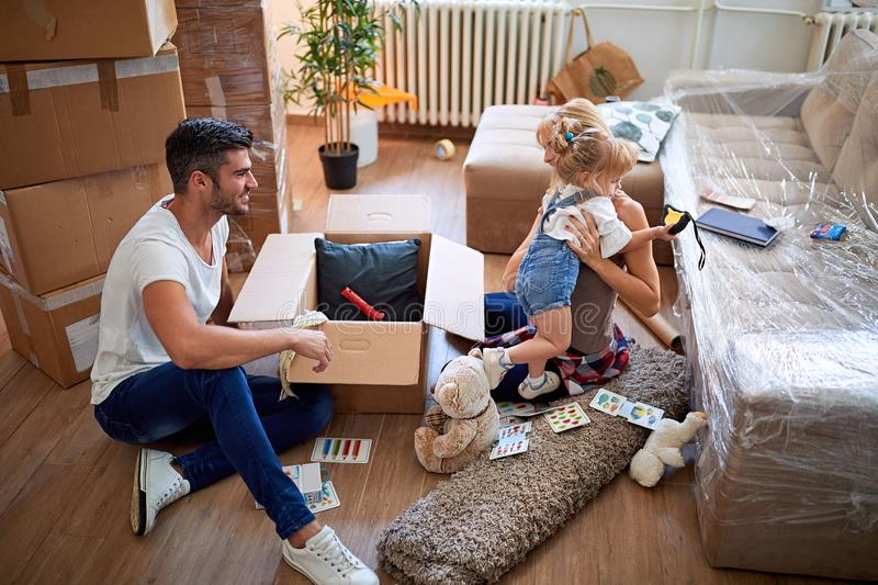 Parents and daughter, unpacking boxes and moving into a new home, having fun royalty free stock photo