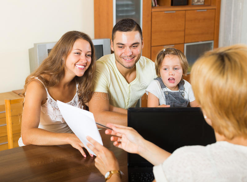 Parents with daughter. Young parents with daughter glad hearing words of social worker stock photos