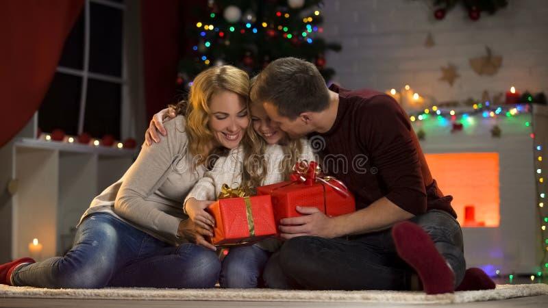 Parents de soin donnant à peu de fille enthousiaste des présents de Noël, tradition de famille image libre de droits