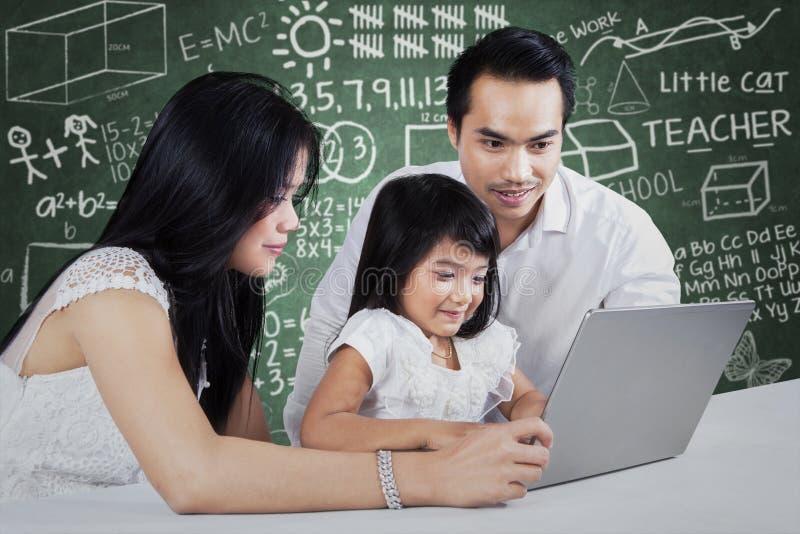 Parents donnant l'éducation d'apprentissage en ligne photo stock