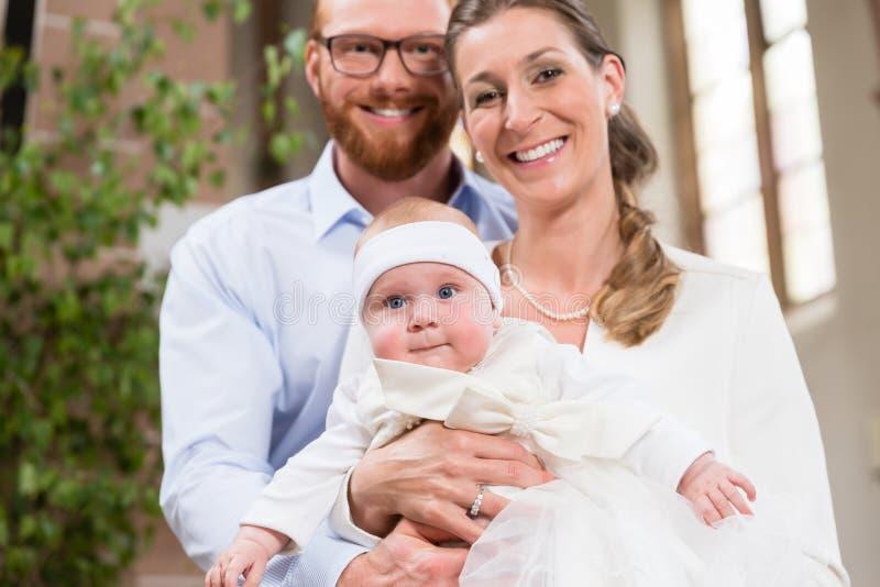 Parents embrassant le bébé au baptême photos libres de droits