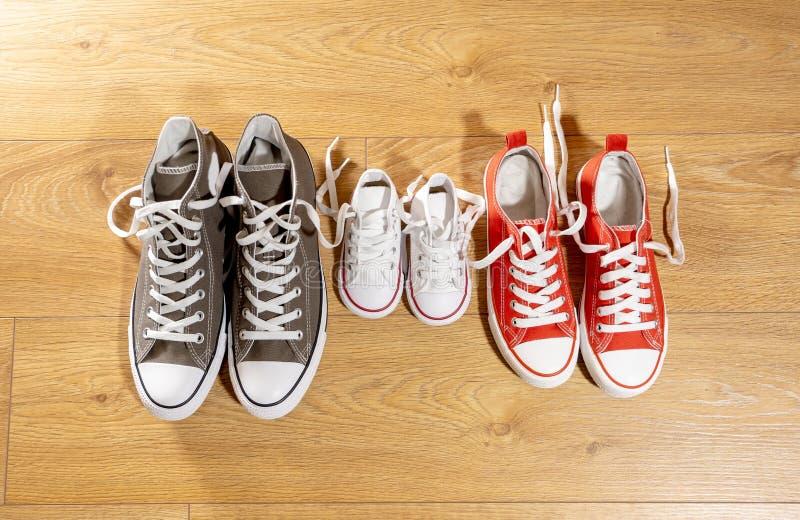 Parents et enfant de chaussures de toile d'espadrilles de famille sur le plancher en bois à la maison dans le mode de vie heureux images stock