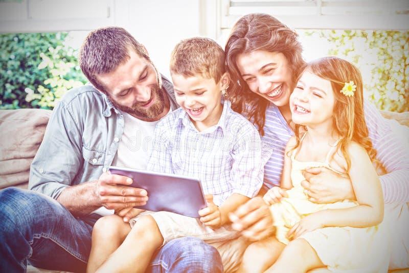Parents et enfants à l'aide du comprimé numérique dans le salon images stock