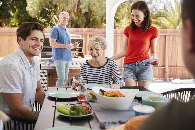 Parents et enfants adultes ayant un barbecue dans le jardin photo libre de droits