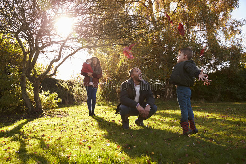 Parents et enfants jouant avec Autumn Leaves dans le jardin photographie stock