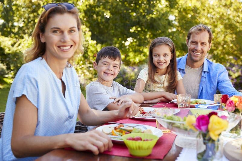 Parents et enfants prenant le déjeuner ensemble dans le jardin photos stock