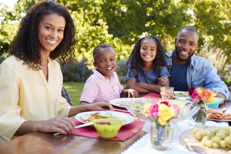 Parents et enfants prenant le déjeuner ensemble dans le jardin image libre de droits