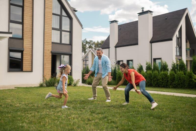 Parents et fille jouant le cache-cache en dehors de la maison proche photographie stock libre de droits