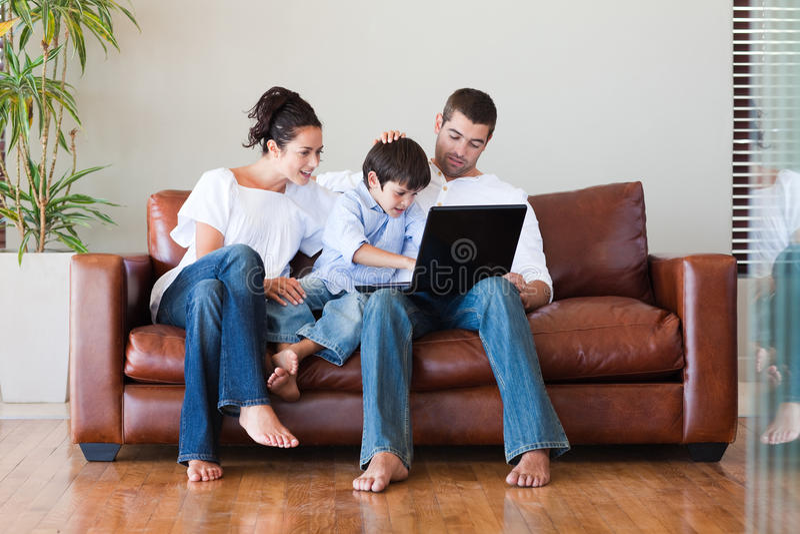 Parents et fils jouant avec un ordinateur portatif photographie stock libre de droits