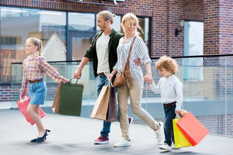Parents et petits enfants marchant avec des paniers photo stock