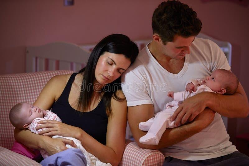 Parents fatigués caressant les filles jumelles de bébé dans la crèche photographie stock