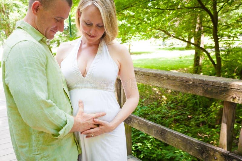 Parents fiers dans l'amour avec le bébé à venir photographie stock libre de droits
