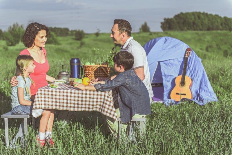Parents gais et enfants mangeant de la nourriture fraîche en nature photo stock