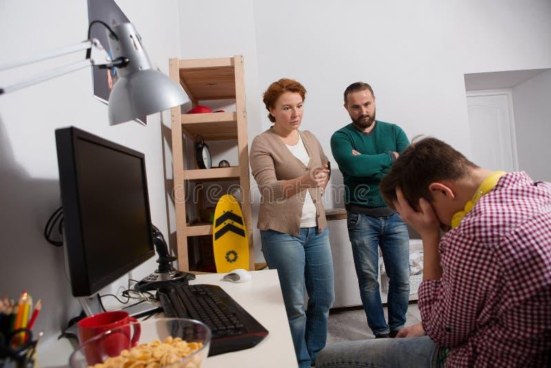 Parents grondant leur fils adolescent dans sa chambre photos stock