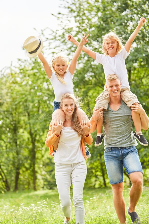 Piggybacking parents with happy children royalty free stock image