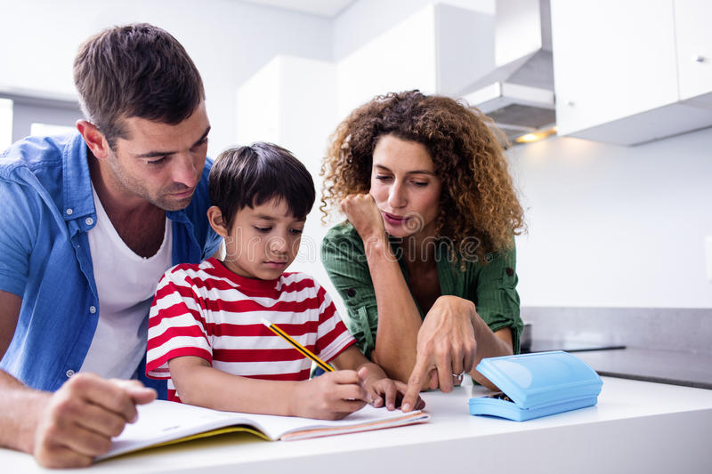 Parents helping son with homework. In kitchen stock image
