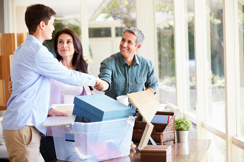 Parents Helping Teenage Son Pack For College. With Father And Son Shaking Hands royalty free stock images