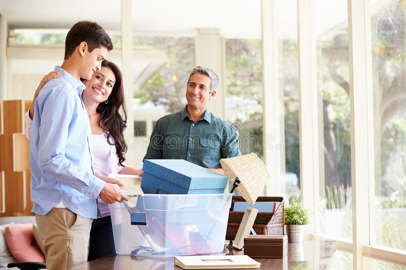 Parents Helping Teenage Son Pack For College. At Home Smiling royalty free stock images
