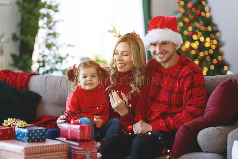 Parents heureux de famille et présents ouverts de fille d'enfant le matin de Noël image stock