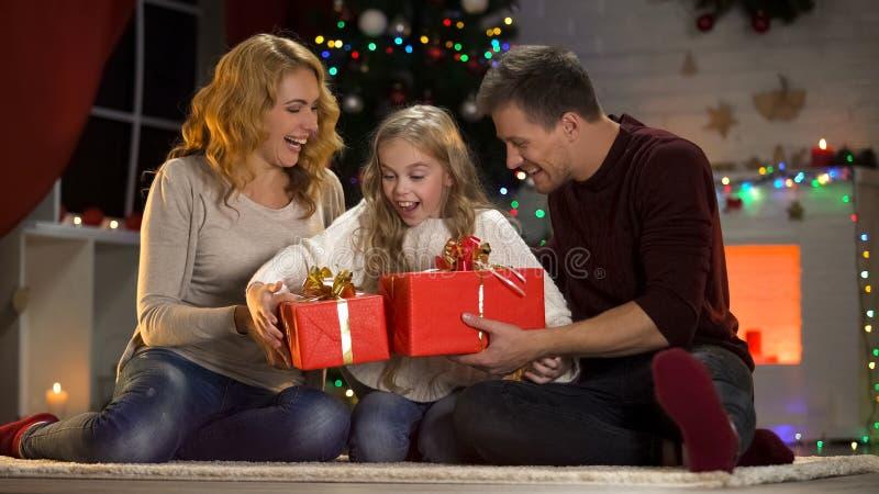 Parents heureux donnant à peu de fille enthousiaste des présents de Noël, tradition de famille images libres de droits