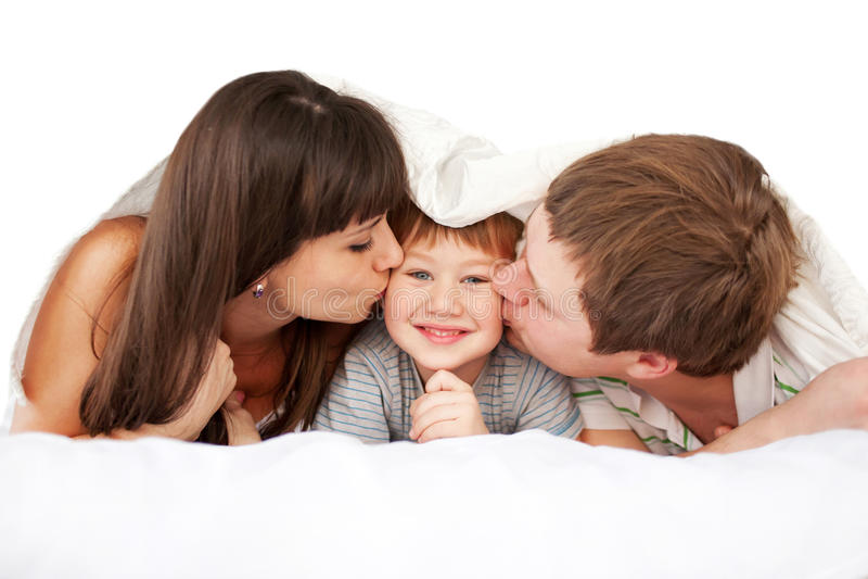 Parents heureux embrassant l'enfant dans le lit photos libres de droits