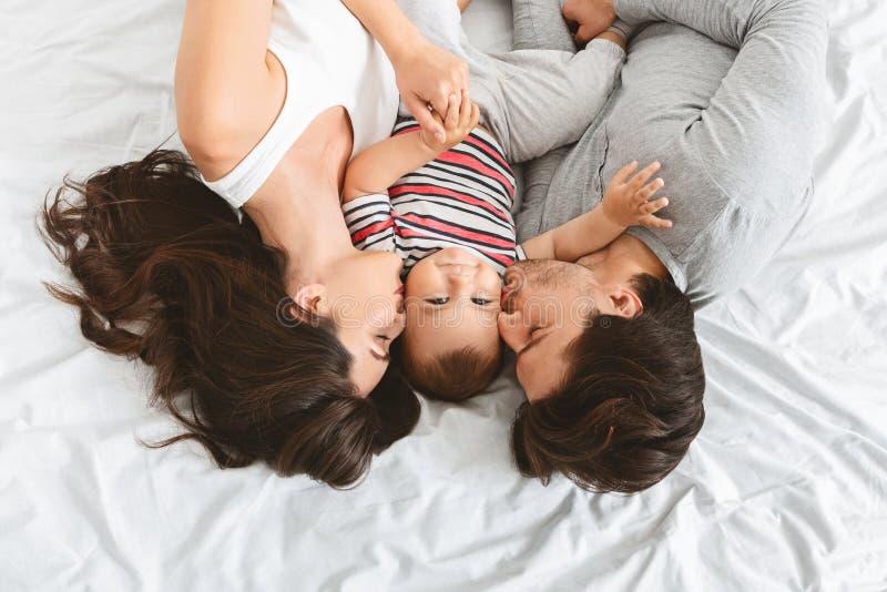 Parents heureux embrassant le fils mignon de bébé dans le lit photo stock