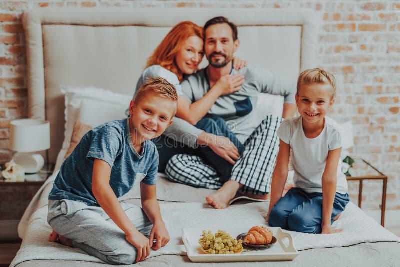 Parents heureux et deux enfants prenant le petit déjeuner photos stock
