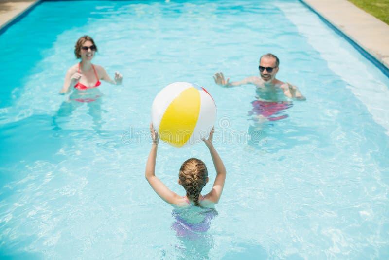 Parents heureux et fille jouant avec la boule de bain dans la piscine images stock