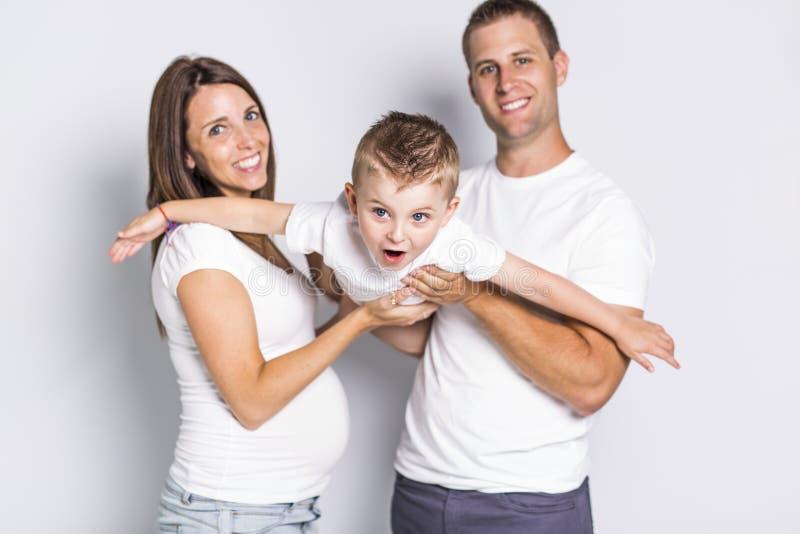 Parents heureux jouant l'avion avec leur garçon d'enfant d'isolement sur le fond blanc photos stock