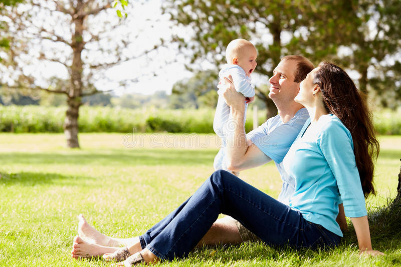 Parents heureux s'asseyant sur l'herbe tenant le fils nouveau-né photos stock