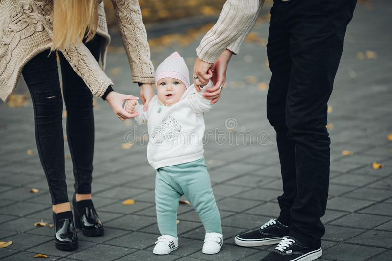 Parents holding satisfied child by hands while it walking. stock photography