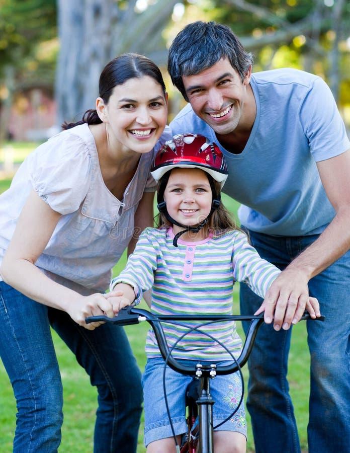 Parents, ihre Tochter beibringend, wie man ein Fahrrad reitet lizenzfreies stockbild