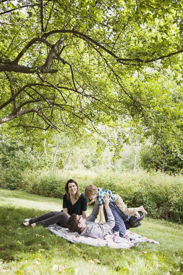 Parents jouant avec l'enfant sur la couverture photos libres de droits