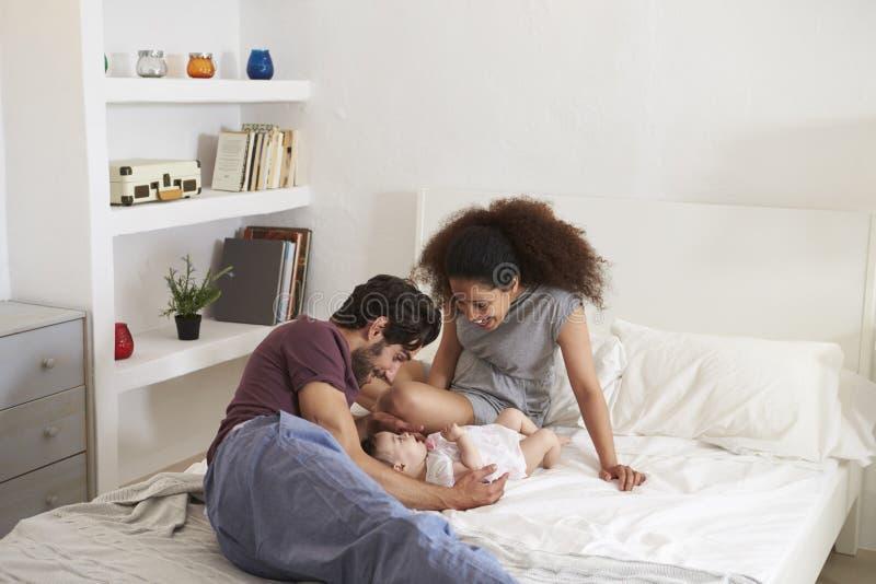 Parents jouant avec la fille de bébé dans la chambre à coucher à la maison images stock