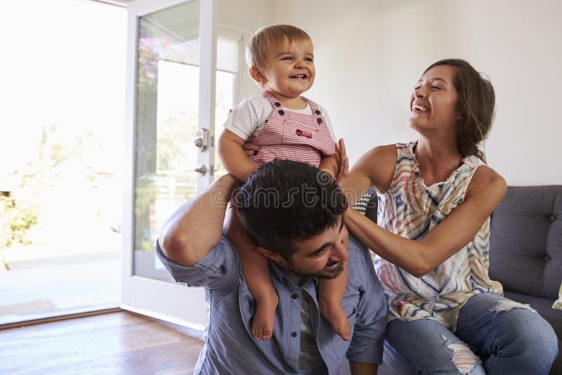 Parents jouant avec la fille de bébé sur Sofa At Home images stock