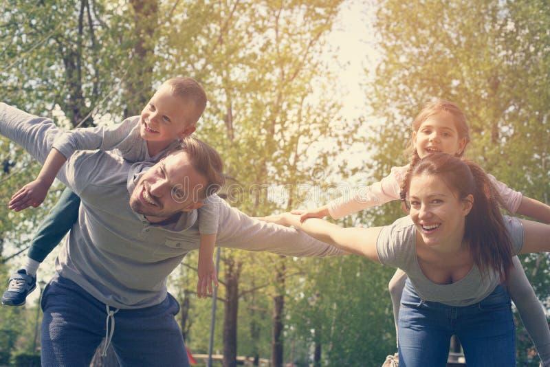 Parents jouant avec leurs enfants en parc regarder est venu images stock