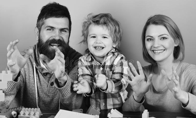 Parents and kid pretend to grab something. Kindergarten and family stock photo